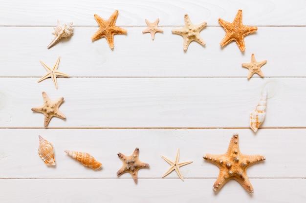 Mise à plat de divers coquillages et étoiles de mer sur une table en bois blanc, vue de dessus. copiez l'arrière-plan de l'espace, concept d'été.