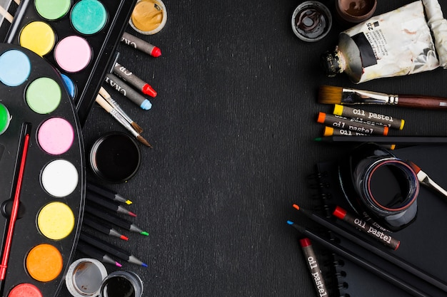 Mise à plat de divers pinceaux et crayons copie espace