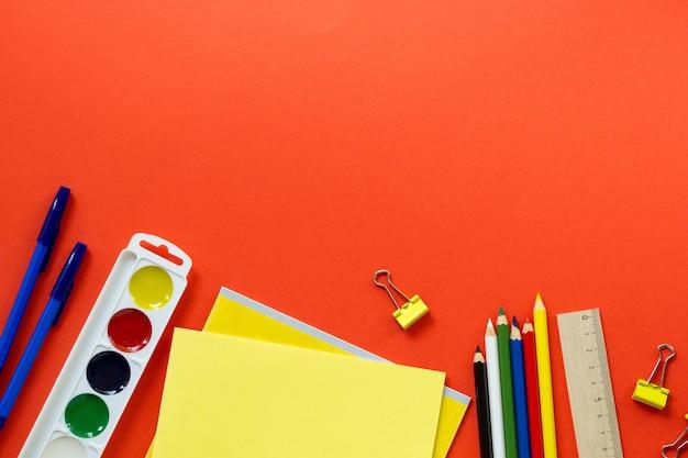 Mise à plat de diverses fournitures scolaires sur fond rouge. espace pour le texte