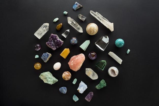 Mise à plat de diverses pierres de cristal sur fond noir. pierres précieuses sur fond sombre. vue de dessus des minéraux curatifs colorés pour la relaxation et la méditation ou la pratique spirituelle