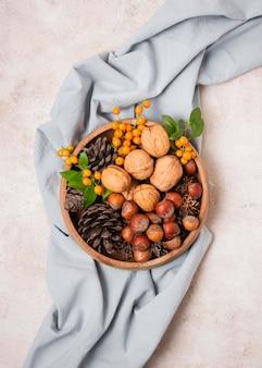 Mise à plat du bol d'automne avec des pommes de pin et du tissu