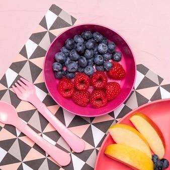 Mise à plat du bol avec des myrtilles et des framboises pour les aliments pour bébés