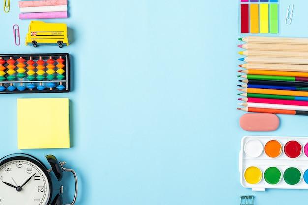 Mise à plat du bureau bleu vif moderne avec des fournitures scolaires sur la table autour d'un espace vide pour
