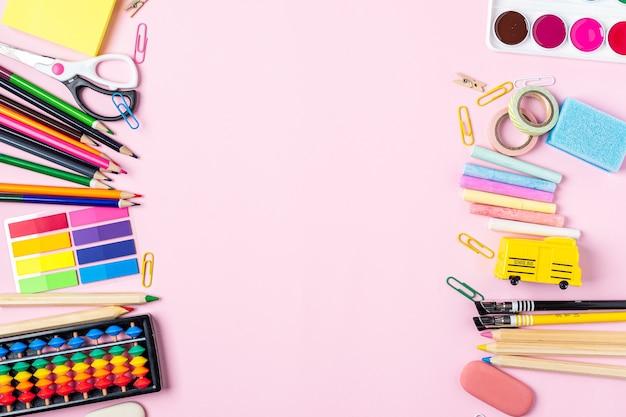 Mise à plat du bureau de bureau rose moderne avec des fournitures scolaires