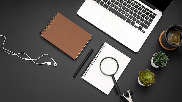 Mise à plat du bureau avec ordinateur portable et loupe