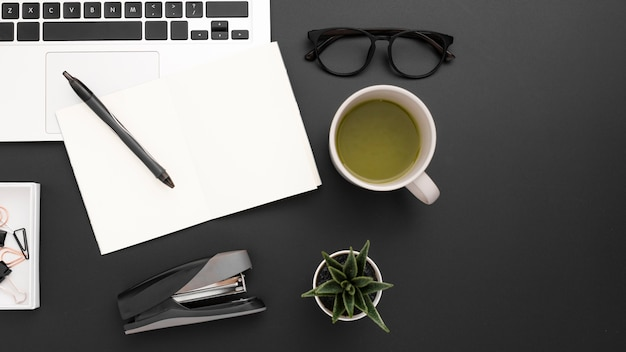 Mise à plat du bureau avec une tasse de thé et un ordinateur portable