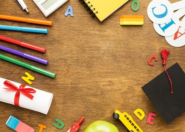 Mise à plat du cahier avec fournitures scolaires et diplôme