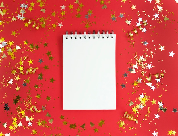 Mise à plat du cahier et d'un stylo sur rouge