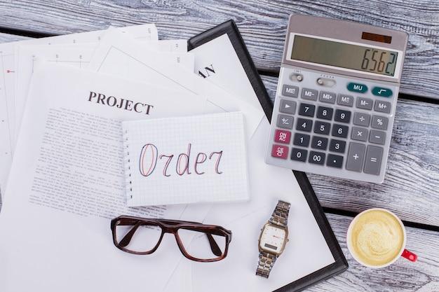 Mise à plat du concept de commande commerciale. calculatrice avec lunettes et montre horloge sur un bureau en bois blanc.