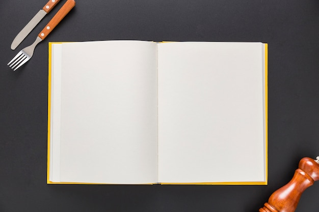 Mise à plat du livre de menu vierge avec des couverts