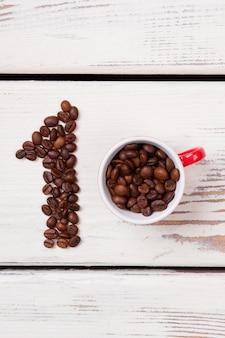 Mise à plat du meilleur concept de café. grains de café torréfiés disposés dans la tasse numéro un et remplissante. vue de dessus.