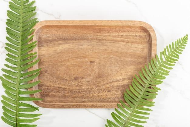 Mise à plat du plateau en bois et feuilles vertes sur fond de marbre blanc. maquette