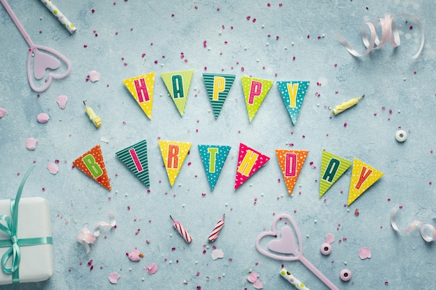 Mise à plat du souhait de joyeux anniversaire en guirlande avec cadeau