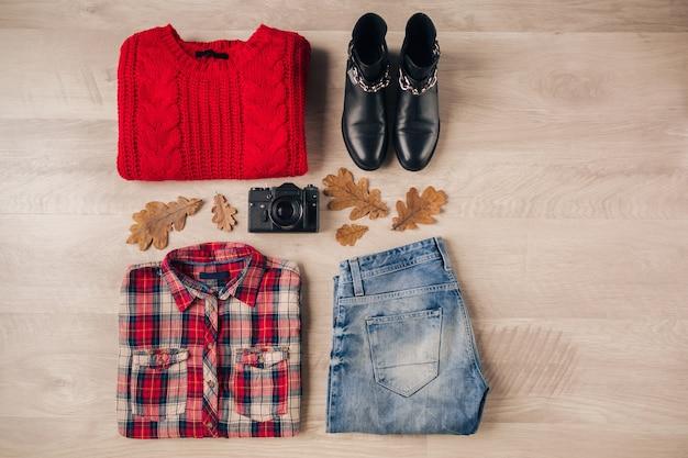 Mise à plat du style femme et accessoires, pull en tricot rouge, chemise à carreaux, jeans en denim, bottes en cuir noir, chapeau, tendance de la mode automne, vue d'en haut, appareil photo vintage, tenue de voyageur