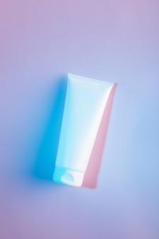 Mise à plat du tube de crème blanche sur fond rose dans une lumière au néon bleu, maquette