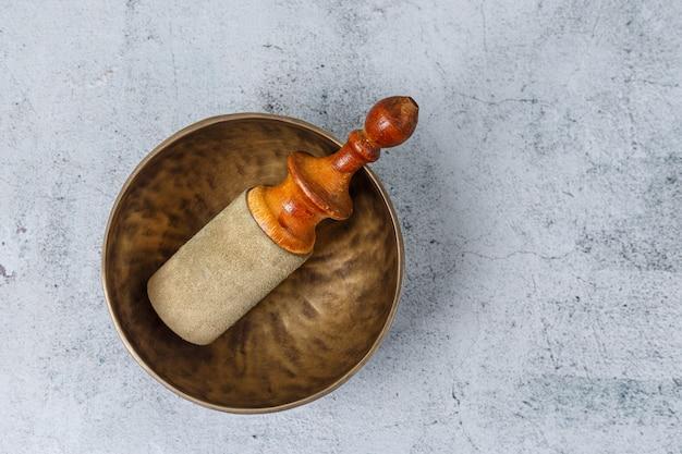 Mise à plat du vieux bol chantant tibétain en métal avec bâton