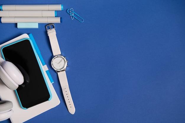 Mise à plat d'écouteurs, smartphone dans un boîtier bleu sur un organisateur blanc, une montre à main, des marqueurs et des trombones isolés sur fond bleu avec espace de copie. vue de dessus des fournitures scolaires de bureau blanc et bleu