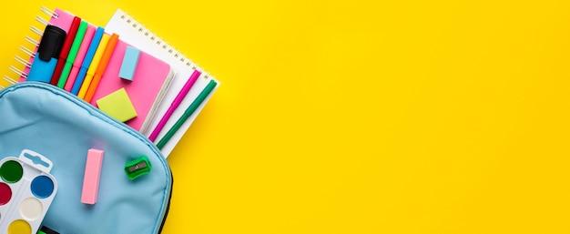 Mise à plat des éléments essentiels de l'école avec des crayons dans le sac à dos et l'espace de copie