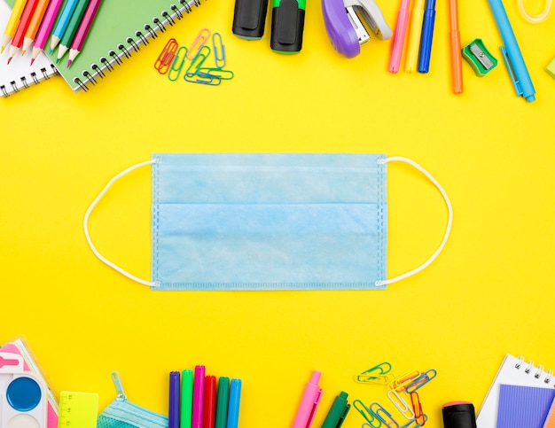 Mise à plat des éléments essentiels de l'école avec masque médical et crayons de couleur