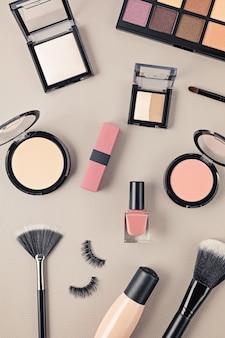 Mise à plat avec ensemble de cosmétiques décoratifs professionnels, outils de maquillage et accessoires femme sur mur gris avec espace copie. concept de blog beauté, mode, fête et shopping. vue de dessus.