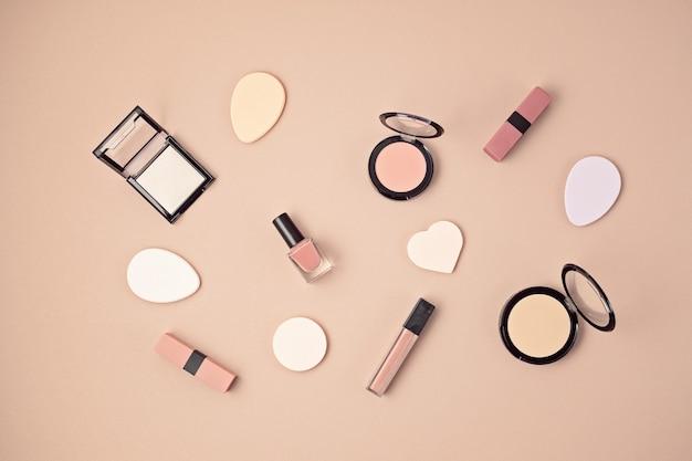 Mise à plat avec ensemble de cosmétiques décoratifs professionnels, outils de maquillage et printemps femme, accessoires d'été sur mur rose avec espace de copie. blog de beauté, mode, fête, concept de magasinage. vue de dessus
