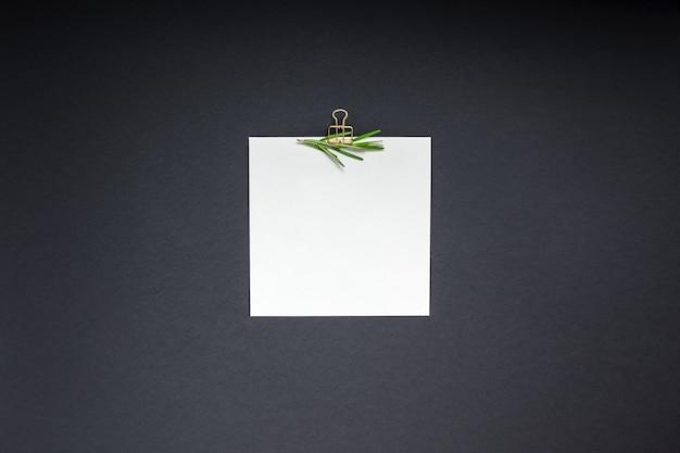 Mise à plat de l'espace de texte de maquette de clip de page de papier vierge sur fond noir avec des herbes vertes et des épices