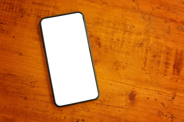 Mise à plat de l'espace de travail en bois avec gadget de téléphone portable. bureau de bureau texturé marron. vue de dessus