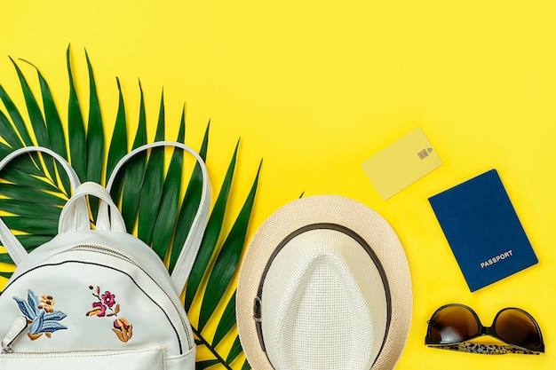 Mise à plat d'été d'accessoires de voyage féminins sur fond jaune. directement au-dessus, copiez l'espace.