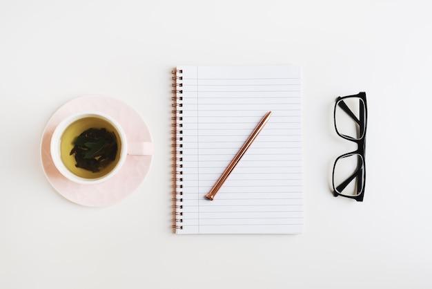 Mise à plat féminine simple avec du thé vert dans un cahier rose avec un stylo en métal et des lunettes de lecture