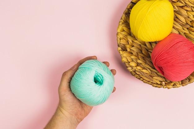 Mise à plat de femme main tenant une belle boule de menthe verte à côté de boules de corail rose et jaune foncé de coton dans un panier avec fond rose pastel et espace copie
