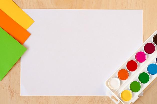 Mise à plat feuille de papier blanc, nouvelles peintures à l'aquarelle, ensemble de couleurs d'automne tendance sur table en bois