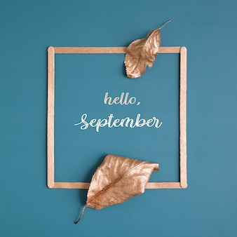 Mise à plat de feuilles d'or et d'un cadre sur fond turquoise avec espace de copie concept minimaliste o...