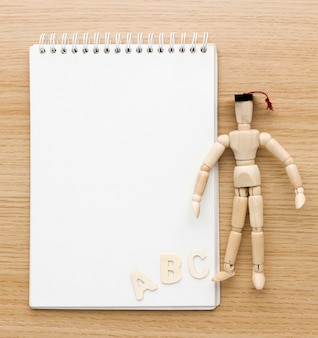 Mise à plat de figurine en bois avec capuchon académique et cahier