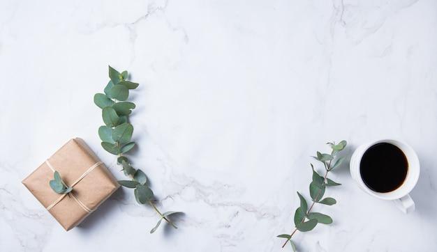 Mise à plat avec fleur d'eucalyptus, tasse de café et boîte d'artisanat présente sur une table en marbre