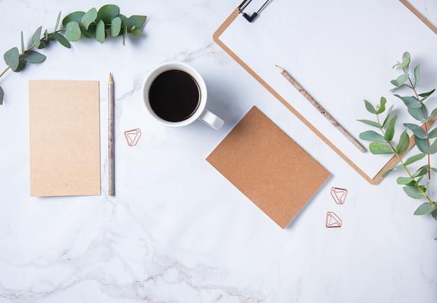 Mise à plat avec fleur d'eucalyptus, tasse de café, un crayon, un cahier artisanal avec des pages blanches sur une table en marbre