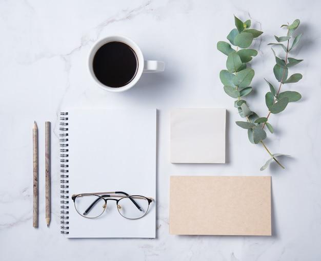 Mise à plat avec fleur d'eucalyptus, tasse de café, un crayon, des verres, un cahier artisanal avec des pages blanches sur une table en marbre
