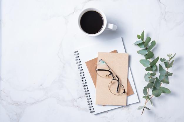 Mise à plat avec fleur d'eucalyptus, tasse de café, verres, un cahier d'artisanat sur une table en marbre