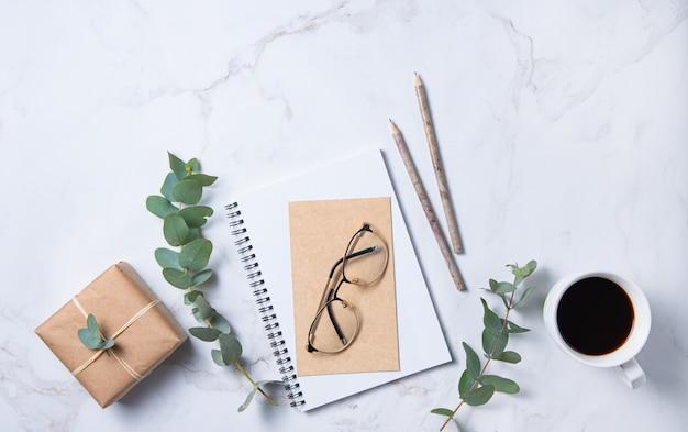 Mise à plat avec fleur d'eucalyptus, tasse de café, verres, crayons, cahier d'artisanat et boîte gigt sur une table en marbre