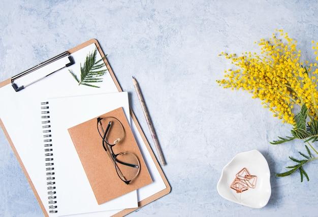 Mise à plat avec une fleur de mimosa jaune, des lunettes, un cahier d'artisanat et des crayons sur une table bleue