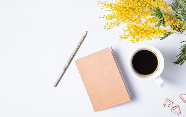 Mise à plat avec fleur de mimosa jaune, tasse de café, cahier d'artisanat et crayon sur une table en marbre