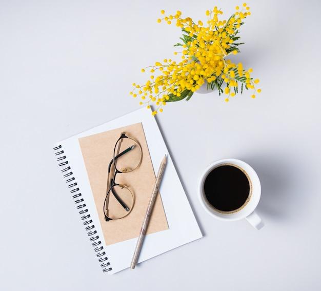Mise à plat avec fleur de mimosa jaune, tasse de café, verres, cahier d'artisanat sur une table en marbre