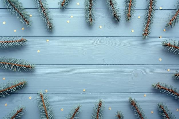 Mise à plat avec fond en bois, épinette argentée et étoiles d'or. fond de noël et nouvel an