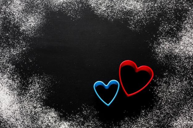 Mise à plat de formes de coeur colorées avec de la farine et de l'espace de copie