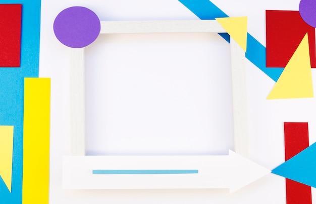 Mise à plat de formes de papier colorées avec cadre et flèches