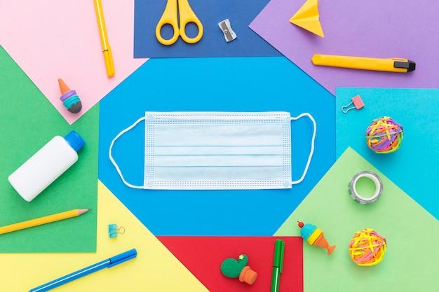 Mise à plat des fournitures scolaires avec masque et crayons