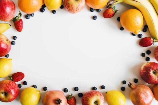 Mise à plat avec des fruits frais et des baies sur fond blanc cadre alimentaire régime à base de plantes
