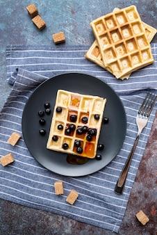 Mise à plat de gaufres couvertes de miel sur une plaque avec des fruits