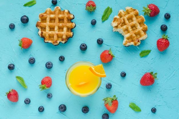 Mise à plat. gaufres, jus d'orange, fruits rouges et feuilles de menthe sur la surface bleue