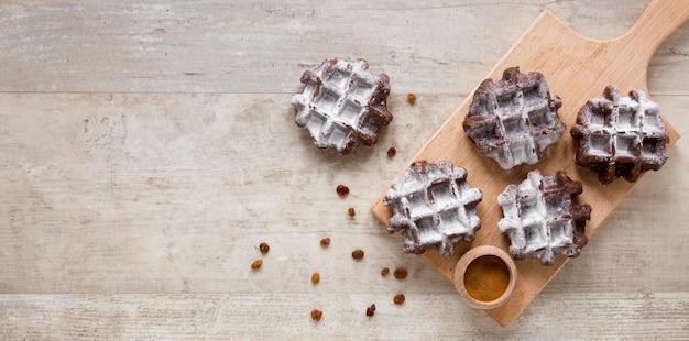 Mise à plat de gaufres sur une planche à découper avec des raisins secs et un espace de copie
