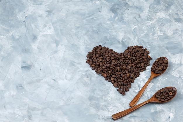 Mise à plat des grains de café dans des cuillères en bois sur fond de plâtre gris. horizontal